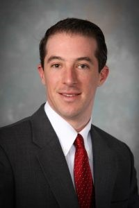 Atty. Michael Colena poses in front of a gray background