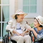 Woman kneels down to speak with an older woman in a wheelchair